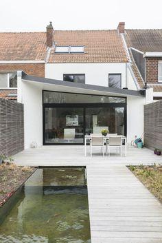 La métamorphose d'une maison sombre des années cinquante en logement minimaliste noir et blanc par MVC Architecten, Belgique