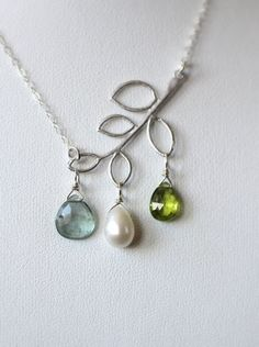 Family Tree Necklace with choice of Three custom gemstones! My modern twist on the family tree necklace. Your choice of three custom gemstones. Shown here with Moss Aquamarine, Pearl and Peridot. Each stone is simply wired to the leaves on the silver branch pendant. A beautiful and unique way to showcase the three people closest to your heart. I hand select my gemstones, they are of the highest quality. Each stone is beautifully cut and faceted! The leaf is positioned on a slight angle and…