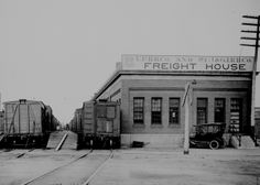 "HISTORIC PHOTO - Taken in about 1918, this photograph shows the freight depot in Grand Island used by the Union Pacific Railroad Company and St. Joseph & Grand Island Railroad Company.  On the dock, workers can be seen loading and unloading the boxcars.  A metal wheelbarrow and automobile are parked in front of the depot. Written on the poll of the railroad crossing sign is, ""Look out for the cars"".  This building still stands in the Union Pacific yards."
