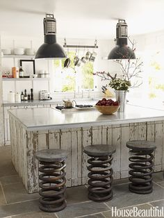 This small kitchen in a Napa Valley ranch cottage also has open shelves, instead of upper cabinets, to give it an airy feel. The shelves and countertops are made of galvanized metal and the cabinetry is made from old fencing. Vintage truck springs, used as stools, were found at Artefact Design & Salvage. Designer and owner of the house Ken Fulk spotted the vintage industrial pendant lights at the Paris flea market.   - HouseBeautiful.com