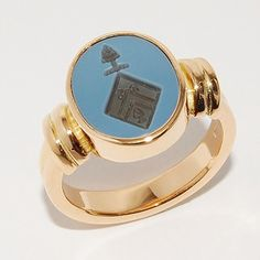 Traditional golden ring with family weapon carved in stone