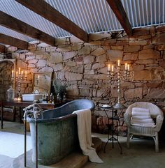 An antique lead bath tub lit by silver candelabras is  beneath a roof of corrugated iron