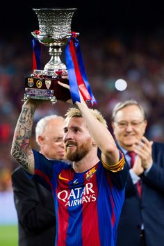 Lionel Messi of FC Barcelona lifts up the trophy after the Spanish Super Cup…