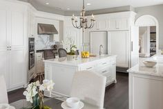 Exquisite Laguna Niguel kitchen features pure white cabinets paired with statuary marble countertops and backsplash.