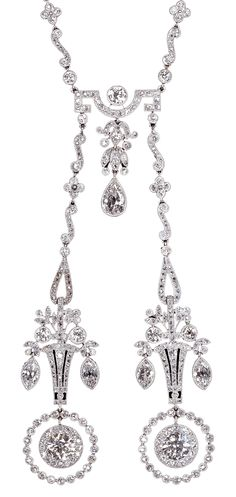 Edwardian platinum millegrain and diamond Lavallière, circa 1910, English. The chain composed of a sequence of quatrefoils, collet set diamonds and S shaped links caught together by a curved bar with Greek fret from which hangs a diamond chain, while to each side the neck chain terminates in twin openwork baskets of flowers finished below with two round diamond in open circles. #Edwardian
