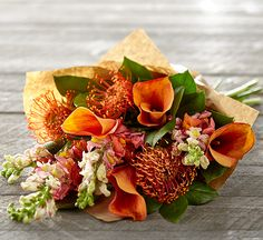 Fluted mango orange calla lilies, columns of blushing snapdragons & bursts of spiny orange pincushion protea