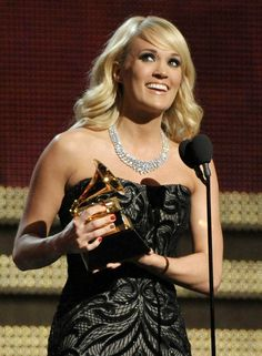 "Carrie Underwood accepts the award for best country solo performance for ""Blown Away."" Underwood is wearing a diamond necklace worth more than $31 million. (Photo: John Shearer / AP) #Grammys"