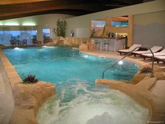 amazing indoor pool wjacuzzi going under the window leading to the outdoor pool