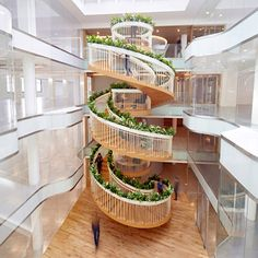 Designer Paul Cocksedge has completed a spiral staircase featuring a garden, a library and a tea bar. The four-storey Living Staircase gets its name from the plants that grow on top of its balustrades and is located in the atrium of Ampersand, an office building for creative technology businesses in Soho, central London.