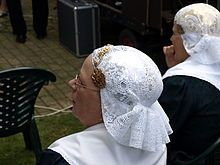 A Dutch cap or Dutch bonnet is a style of woman's hat associated with the various traditional Dutch woman's costumes. Usually made of white cotton or lace, it is sometimes characterized by triangular flaps or wings that turn up on either side