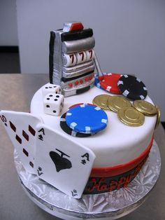a gambling themed cake, with slot machine, poker chips and playing cards