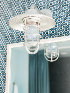 In keeping with the maritime feel of the bathroom, this light sconce resembles those found on ocean going vessels.