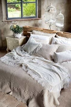 Rustic bedroom - gorgeous looking bedding with pattern gives it a cozy feel and bird cages finish this shabby chic decor.