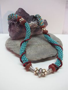 This 21 Japanese style Kumihimo necklace is woven with turquoise, copper, and gold lined seed beads. The Maasai tribal beads influenced the design