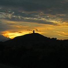 Glastonbury Tor at Sunset. Lady Fenella has 9 days to cross a dangerous world or magic, find her cousin, and reach Glastonbury before the veil between worlds descends again. The Beltane Escape by Ariella Moon. http://www.AriellaMoon.com