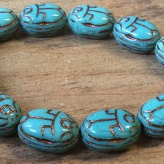 18mm X 12mm scarab beads in turquoise and bronze wash.