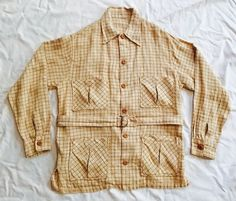Wonderful 1920s-1930s belted sporting jacket in window pane linen. Great condition with beautiful pockets, belted waist, wood button front and cuffs and great back detailing down the center back.