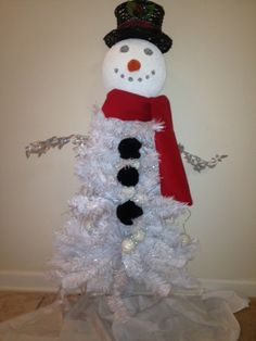 Snowman Christmas Tree. Decor hat from Micheals, styrofoam ball painted with snow paint. Sharpie eyes and mouth on. Orange felt material shaped like a cone and glued on. Red felt wrapped around. Silver leaves as arms. Black pom poms for buttons and white tree.