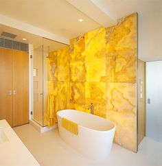 view of tub and shower in front of backlit Honey onyx wall