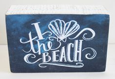 "Who doesn't Love the Beach? With a scallop shell shaped heart in place of the word Love this wood block sign made to mimic chalkboard art is a fun accent piece. Measuring 4.5""w x 3""h x 1.75""d it makes a great gift, party favor or conversation starter!  Primitives by Kathy from California Seashell Company"