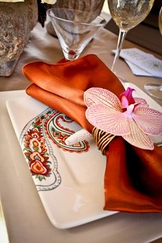 Burnt orange napkin with an orchid accent.