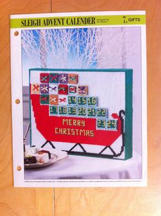Sleigh Advent Calendar. Decorative Christmas Holiday Calendar with Santa's sleigh and gifts stitched in 7-mesh plastic canvas.