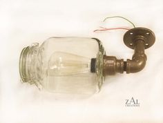 Wall Light made from hinged lid (clamp lid) square glass jar and plumbing fittings. Approximate measurements: 13 (Tall) x 6 1/2 (Deep) x 5 (Wide). Square jar is 5 x 5 x 8. Round mounting flange is 3- 3/8 in diameter. 4-1/2 diameter flange available if Light Fixture is to be mounted to