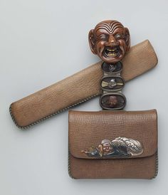 Tobacco-pouch; netsuke; kanamono; inner plate with Chinese child reading a book and another figure with Chinese hat and fan; leather pipe-case. Japanese Edo period–Meiji era mid to late 19th century (before 1889) - Gyokuryushi Yasumasa http://www.mfa.org/collections/object/tobacco-pouch-netsuke-kanamono-inner-plate-with-chinese-child-reading-a-book-and-another-figure-with-chinese-hat-and-fan-leather-pipe-case-10097