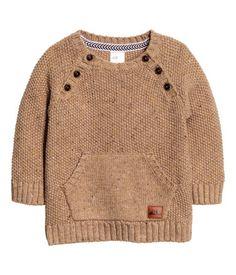 Lichtbruin. Een trui van een zachte katoenmix waarin wol is verwerkt met een ingebreide structuur. De trui heeft knopen voor, raglanmouwen, een kangoeroezak