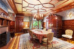 This is the formal dining room, with real 24 karat gold leaf on the ceiling and red floral details. Original stained glass windows face out onto the garden. This room is rich with mahogany, with original cabinetry and an intimate fireplace seat. The walls are upholstered in iridescent denim-blue. The dining room also enjoys a gas fireplace, with a brick surround and a mahogany header, flanked by two of the lovely sconces that you'll see all over the house. Price: $29,000,000.