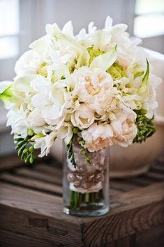 The lime green hydrangea makes the perfect background for the peach toned peonies, white Oriental lilies and white freesia in this arrangement.