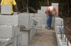 Masonry construction workers building cinderblock wall