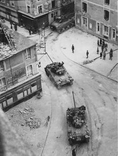 A view looking down from a church steeple as a M4A1 Sherman and pair of Sherman Firefly tanks pass through Douvres-la Delivrande, in Normandy, France. 8 June 1944.