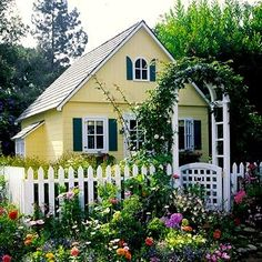 picket fence and trellis with vines and flower garden surrounds two-story playhouse