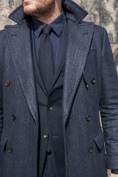 Navy themed suit and overcoat that is right on trend