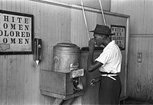 """Jim Crow laws were state and local laws enforcing racial segregation in the Southern United States. Enacted after the Reconstruction period, these laws continued to be enforced until 1965. In this image, an African-American man drinks at a """"colored"""" water fountain in a streetcar terminal in Oklahoma City, Oklahoma, 1939."""