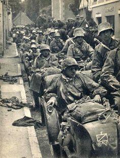 Una columna de la motocicleta de las Waffen-SS se detuvo en la calle con un caballo soldados montados en el fondo 1940.