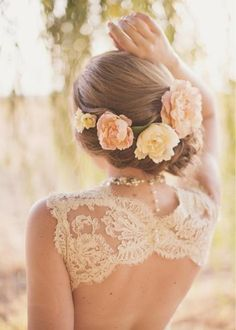 A lace back and hair pined up with peach flowers.