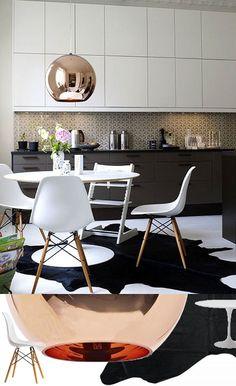 Une cuisine noire et blanche même pas froide grâce au bois des chaises DSW, à la suspension cuivrée Copper Shade et au (sublime) tapis peau de vache noir