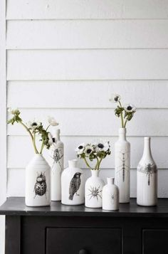 As garrafas aqui foram pintadas de branco, com uma découpage em P&B. / Crédito: Pinterest.