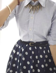 Gotta love the polka dotted skirt with the belted waist with the spiky necklace for a bit of edge.