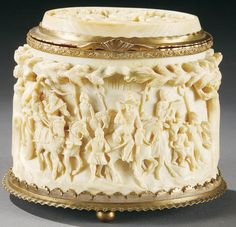 SOUTH GERMAN CARVED IVORY AND GILT-COPPER MOUNTED LIDDED BOX, the sides carved in high relief depicting scenes of travelers in a wooded landscape. The hinged lid with gilt copper mounts and inset with oval ivory plaque carved in high relief and depicting travelers at rest. Set in a base of gilt-copper and resting on ball feet.