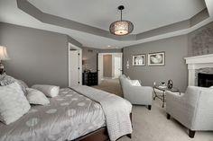 Contemporary Master Bedroom with Built-in bookshelf, Jonathan adler duvet cover, Cement fireplace, flush light, Carpet