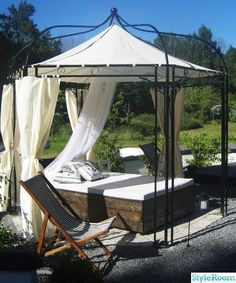 cute pavilion over outdoor mattress bed with white curtains.