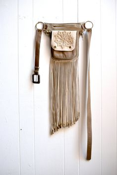 Leather Fringe Belt Bag Revivall Clothing's convertible leather Hip Bag can be worn two ways- as a belt or across your shoulder as a crossbody bag. They are perfect for traveling, festivals, a night out dancing, or just casually around town. There are 3 large pockets- an outer patch pocket with snap closure, a larger zipper pocket behind it, and 2 slip pockets in the very back. The zipper pocket will fit a mini iPad. I like to use the slip pocket to put receipts, papers, or things you need…