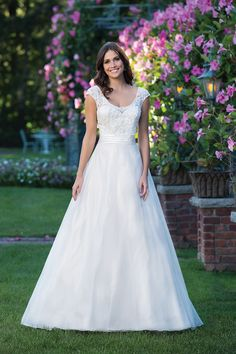 Inspired by a fairy tale, this A-line gown features a scoop neckline, beaded applique lace bodice, natural waistline accented by a Satin cummerbund, and an organza skirt with chapel length train.