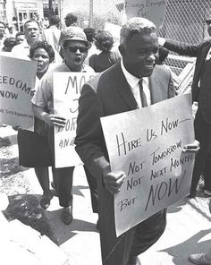 """""""Hire Us Now -- Not Tomorrow, Not Next Month, But NOW."""" Pictured here is the baseball player Jackie Robinson, who was also a dedicated civil-rights activist. Robinson marched alongside the Rev. Martin Luther King Jr. and other leaders. Here Robinson joined a Congress of Racial Equality protest, picketing construction of the publicly funded hospital and decrying its discriminatory hiring practices, August 1963. (Downstate Medical Center, 450 Clarkson Ave.) Source: Associated Press"""