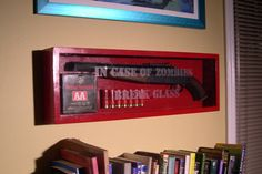 OSHA-red box mounted on wall, with glass faceplate bearing etched words IN CASE OF ZOMBIES BREAK GLASS.  Within are a shotgun, some loose sh...