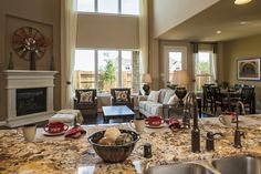 The kitchen overlooks this family room with a lovely fireplace at Riverstone Ranch - Estate Plus. #MeritageHomes #Houston
