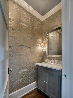 Gray powder room boasts a gray ceiling over walls clad in silver and gray fish wallpaper lined with a beveled mirror over a gray wash vanity topped with gray and white marble.